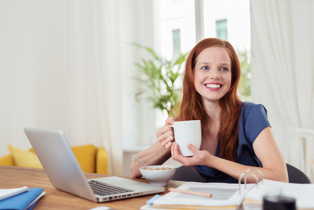 Thoughtful Young Woman Having her Breakfast at her Home Office, Showing Happy Facial Expression.